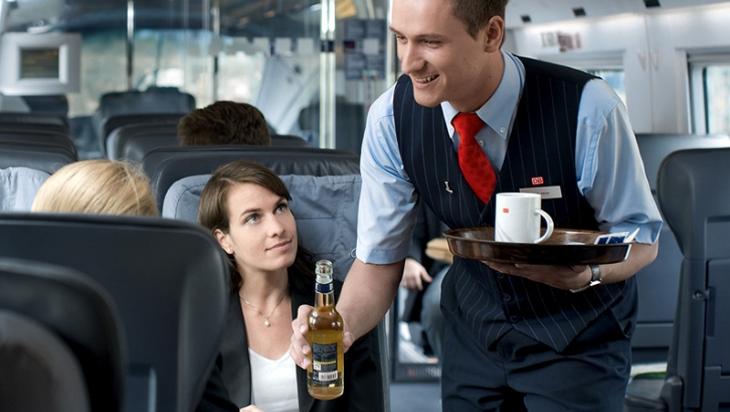 Ein Mitarbeiter im Bordservice serviert Kaffee © DB AG/Max Lautenschläger