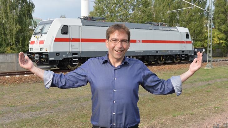 Mathias Semrau und im Hintergrund die Lok für den IC2 – weiß mit rotem Streifen; Bild: DB/Jet-Foto