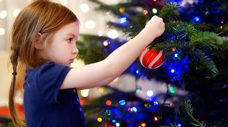 Kleines Mädchen schmückt den Weihnachtsbaum © Shutterstock